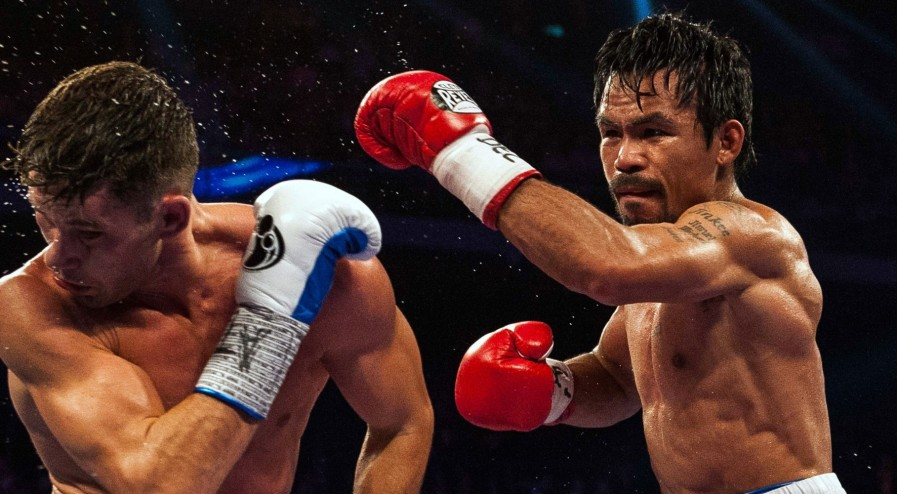 Manny Pacquiao of the Philippines (R) fights against Chris Algieri of the US during their World Boxing Organization welterweight title bout at the Cotai Arena in Macau on November 23, 2014. AFP PHOTO / XAUME OLLEROS        (Photo credit should read XAUME OLLEROS/AFP/Getty Images)